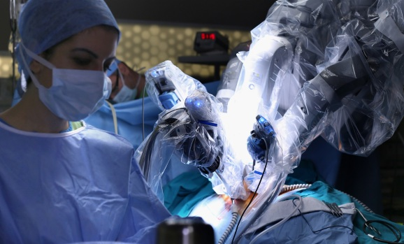 A robot performs surgery while a doctor overseas the procedure.