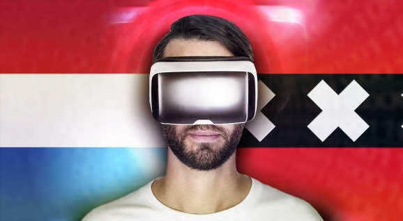 A man in virtual reality headset stands in front of a flag of The Netherlands.