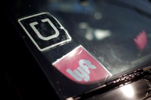 A driver displays Uber and Lyft ride sharing signs in his car windscreen in Santa Monica, California, U.S., May 23, 2016.