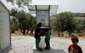 This is a photo of Children stand around a solar powered charging station for mobile devices designed by a group of university students, at the municipality-run camp of Kara Tepe on the island of Lesbos, Greece, June 14, 2016.