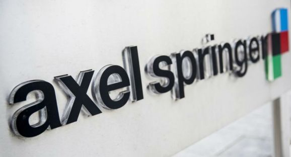 The logo of the German publisher Axel Springer is seen outside its headquarters in Berlin in this August 7, 2013 file photo.