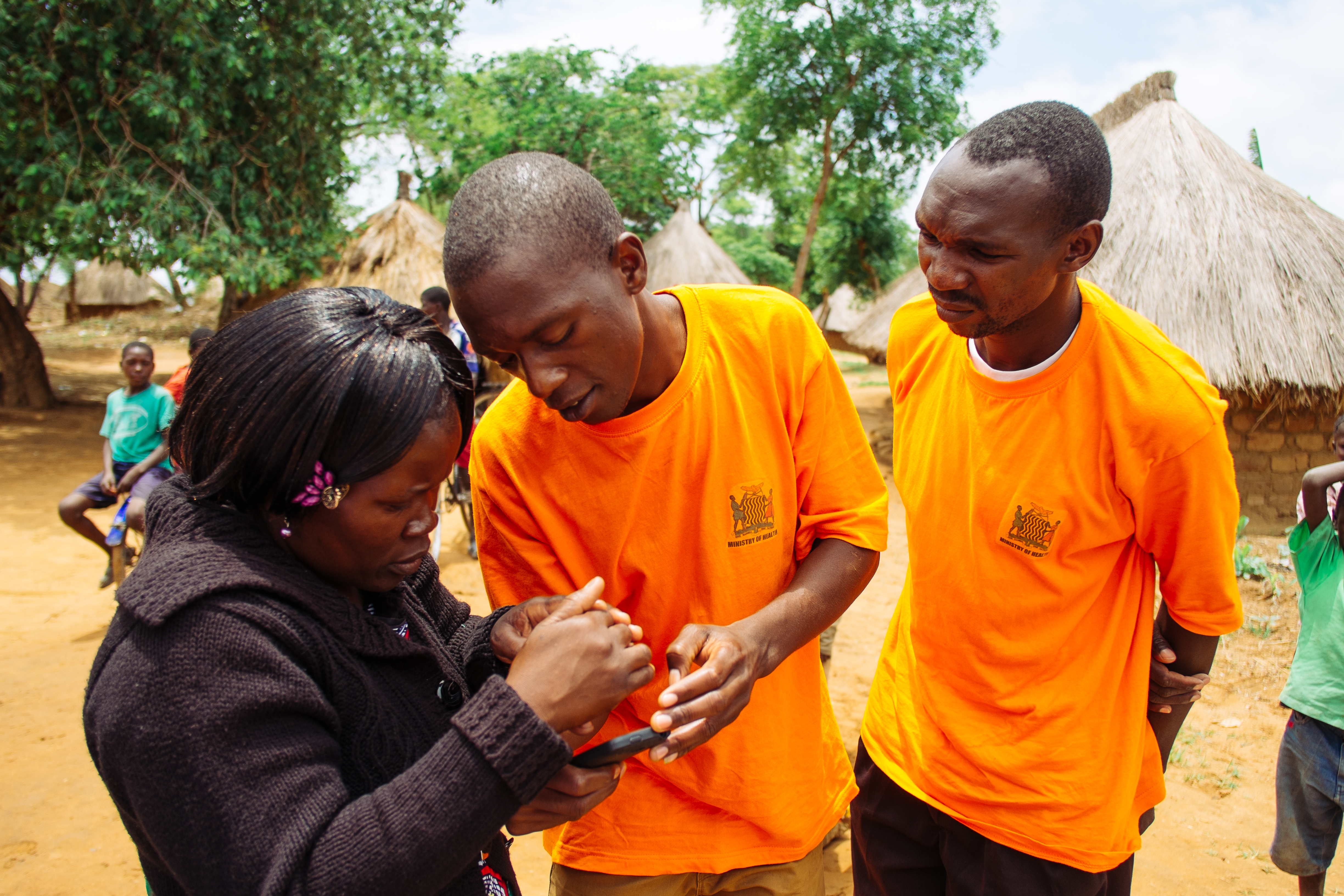 Ephraim Sikalundu (center), Data collector, and Vincent Munsaka (right), Community health worker, stand with Rachel Mokosha (left), District Malaria Focal Person, looking mobile phone data.