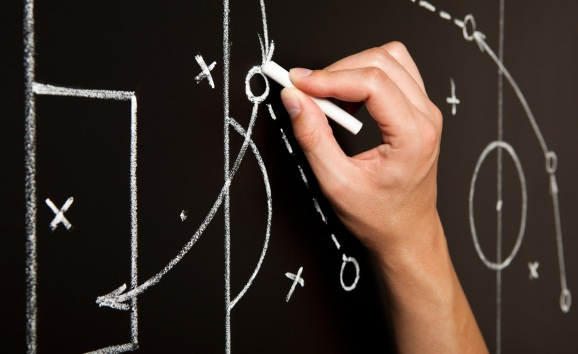A coach drawing football plays on a chalk board