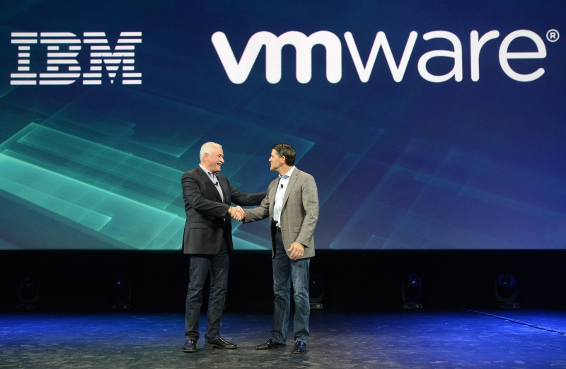 Robert LeBlanc, left, senior vice president of IBM cloud, shakes hands with Carl Eschenbach, formerly president and chief operating officer of VMware.