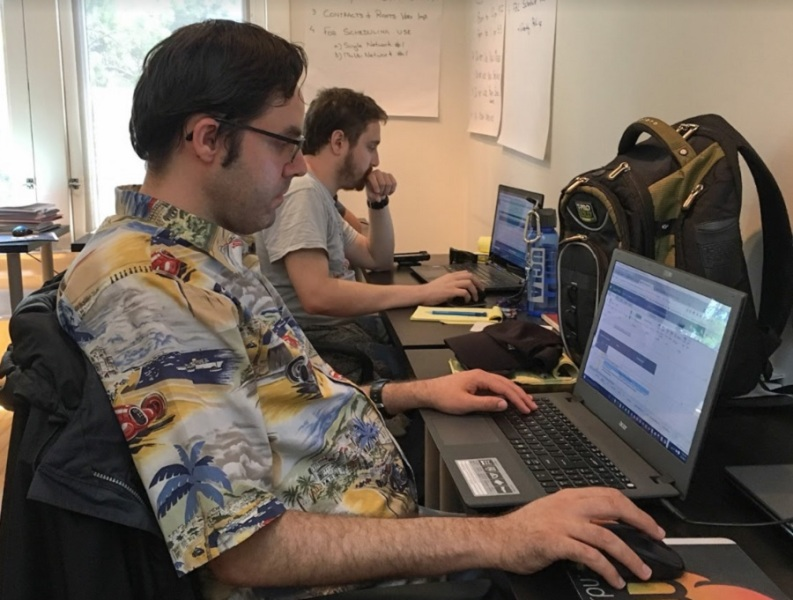 Members of MindSpark's team help debug software.