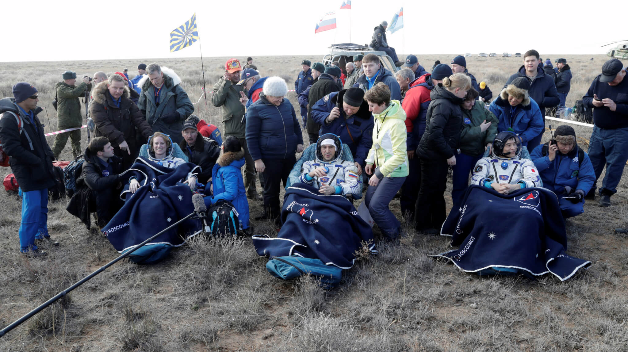 The International Space Station (ISS) crew members Kate Rubins of the U.S., Anatoly Ivanishin of Russia and Takuya Onishi of Japan, surrounded by ground personnel, rest shortly after landing of the Russian Soyuz MS space capsule near the town of Dzhezkazgan (Zhezkazgan), Kazakhstan, October 30, 2016. REUTERS/Dmitri Lovetsky/Pool