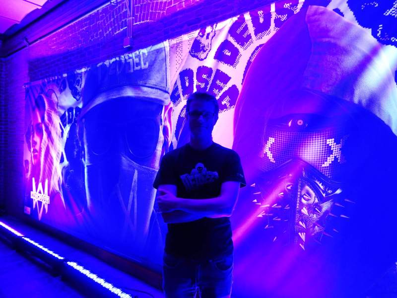 Dominic Guay, senior producer on Watch Dogs 2, stands before an image of Marcus Holloway.