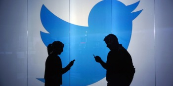 People standing against a wall bearing Twitter's logo.