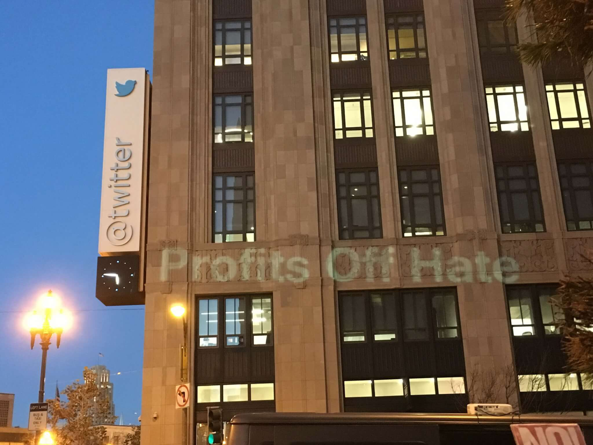 Activists protesting in front of Twitter project message saying that the company profits off of the hate expressed by Trump.