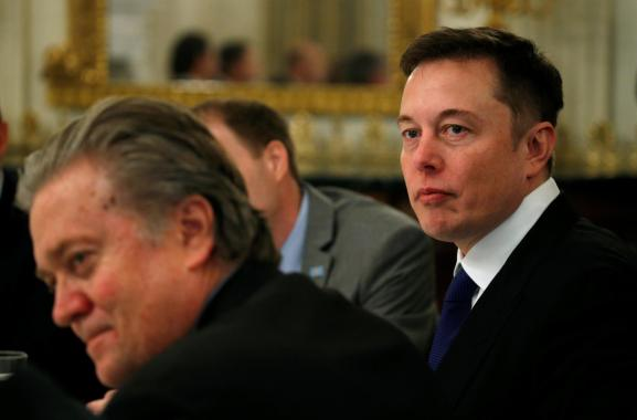 Tesla CEO Elon Musk (R) sits beside senior counselor to the president at the White House on February 3, 2017.
