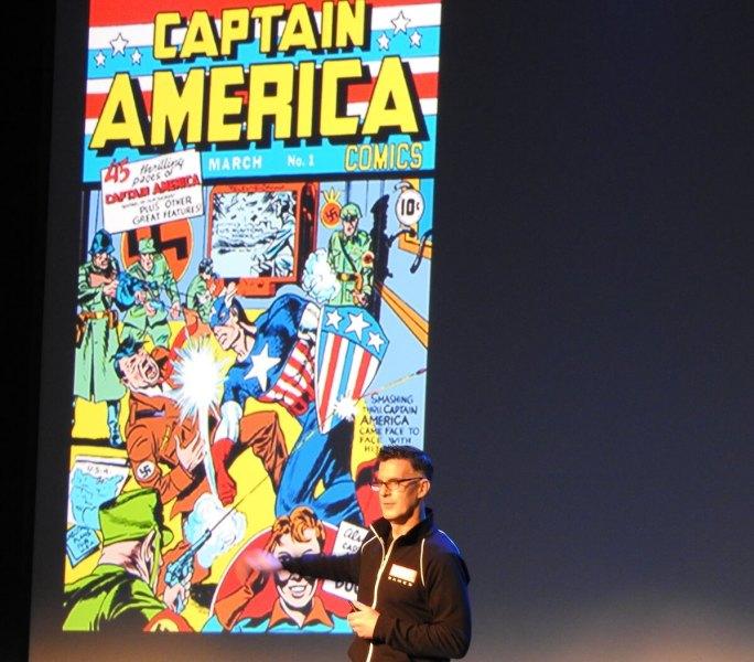 Bill Rosemann standing next to an image of the original Captain America.