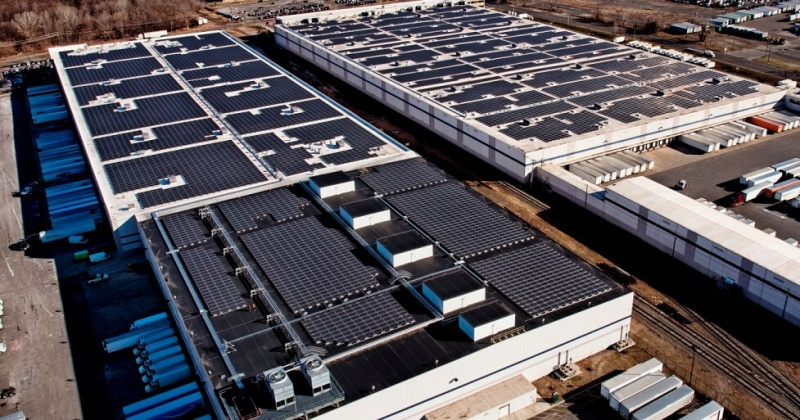 Aerial view of two Amazon fulfillment facilities with solar systems on their rooftops.