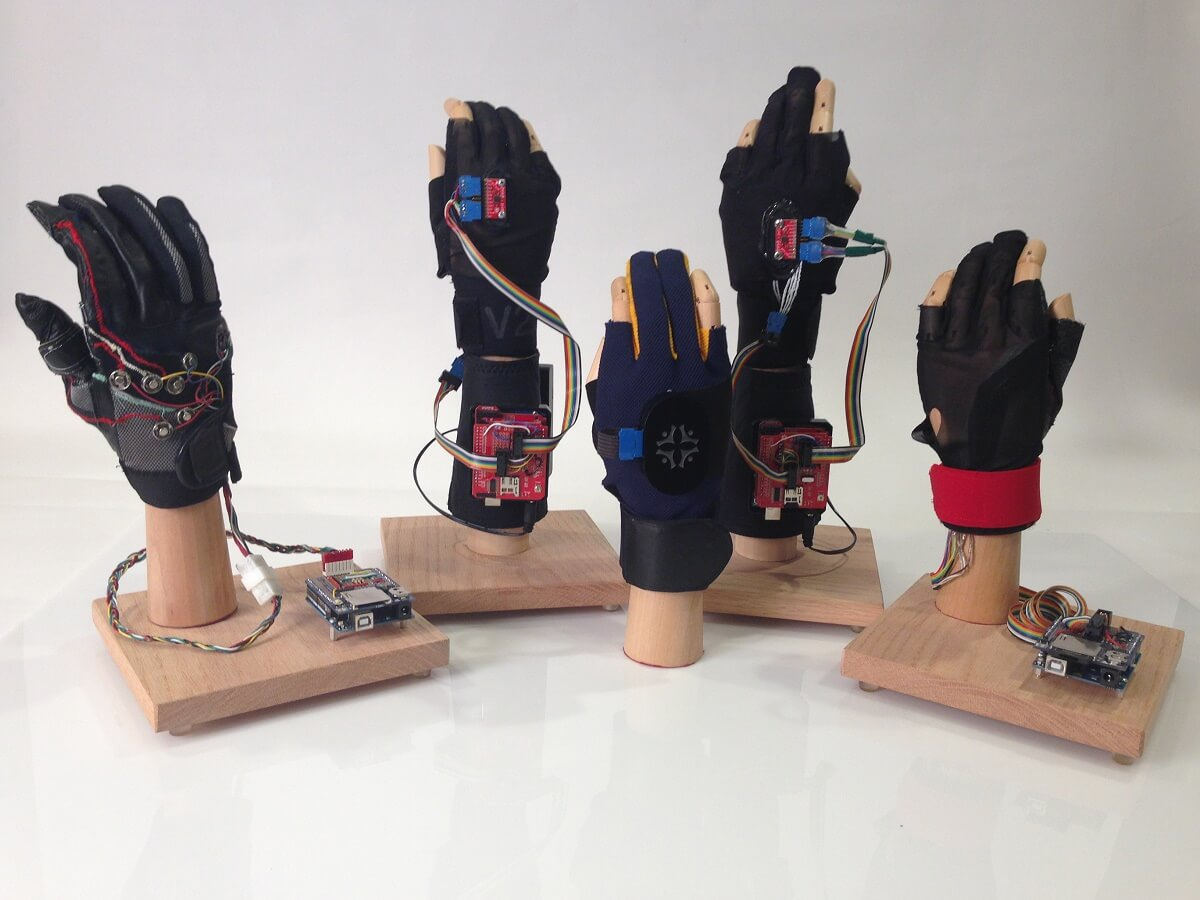 Proof of concept glove (far left) Wired prototypes using arduino (back row) Wireless Bluetooth Glove used on A.mericas Greatest Makers (front center)