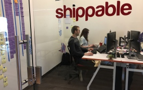 A photo shows Shippable's logo on a glass wall at the company's office