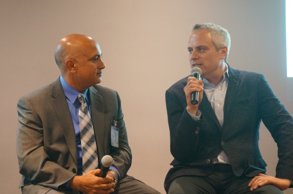 A photo shows Brad Stone and Vish Makhijani speaking with one another.