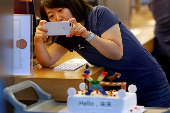 A member of Apple staff takes pictures as new iPhone X begins to sell at an Apple Store in Beijing, China November 3, 2017.