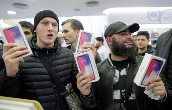 First customers to buy Apple's new iPhone X pose during its global launch at a cell phone store in central Moscow, Russia November 3, 2017.