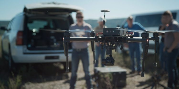 A man stands in a field operating a PrecisionHawk drone
