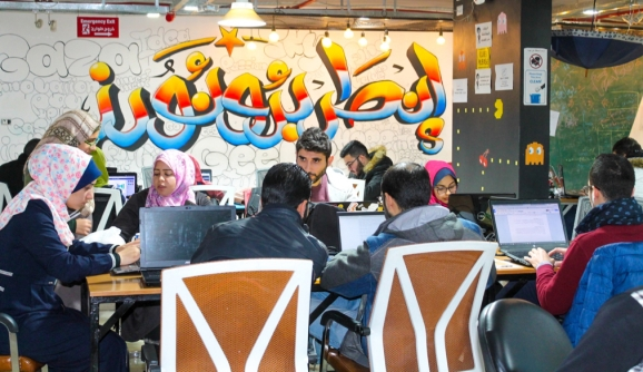 "People working at the Gaza Sky Geeks coworking space in front of graffiti that says ""entrepreneurs"" in Arabic."