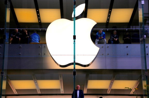 A customer stands underneath an illuminated Apple logo as he looks out the window of the Apple store located in central Sydney, Australia, May 28, 2018.