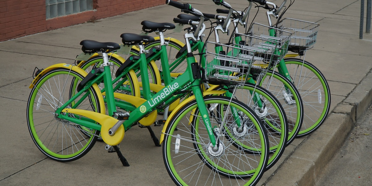 Dallas, TX / USA 2/7/2018 – Lime bikes are lined up on the sidewalk ready for a rider to unlock one and go.