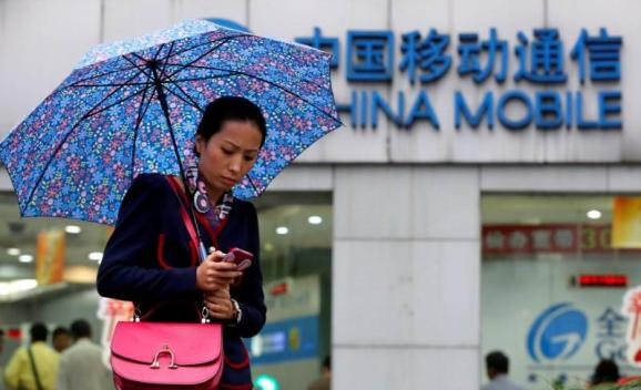 FILE PHOTO: A woman uses her mobile phone in front of a China Mobile office in downtown Shanghai October 22, 2012.   REUTERS/Aly Song/File Photo