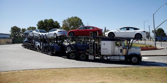 A car carrier trailer carries Tesla Model 3 electric sedans, is seen outside the Tesla factory