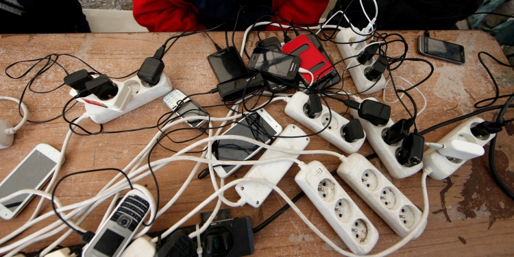 Migrants charge their mobile phones with a generator at the Calais refugee camp