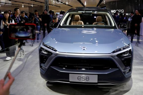 Visitors check NIO ES8 displayed during a media preview of the Auto China 2018 motor show in Beijing, China April 25, 2018.