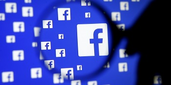 A man poses with a magnifier in front of a Facebook logo on display in this illustration.
