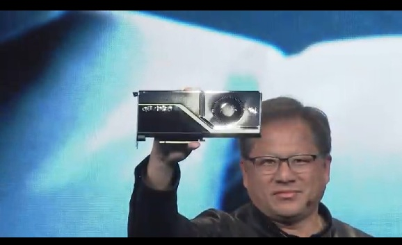 Jensen Huang shows off a Quadro RTX GPU.