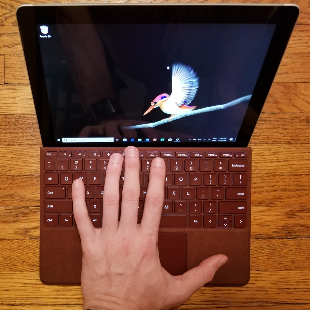 Surface Go with a left hand on the red Alcantara keyboard