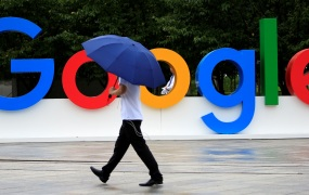 A man with an umbrella walking in front of a Google sign