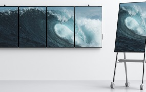 Four Microsoft's Surface Hub 2 devices on a wall and one on a stand