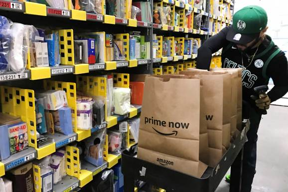 An employee collects items ordered by Amazon.com customers through the company's two-hour delivery service Prime Now in a warehouse in San Francisco, December 20, 2017.