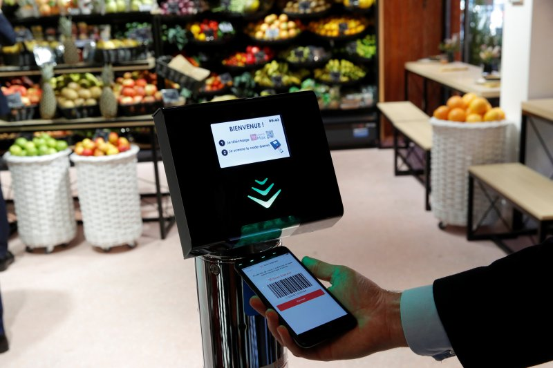 """A man holds his smartphone and a Casino App at a self-scanning terminal which replaces a cashier as he shops inside a high-tech store named """"Le 4 Casino"""" in Paris, France, October 4, 2018."""