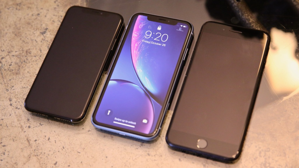 The iPhone XR sits between the iPhone XS (left) and an iPhone 7 Plus (right).