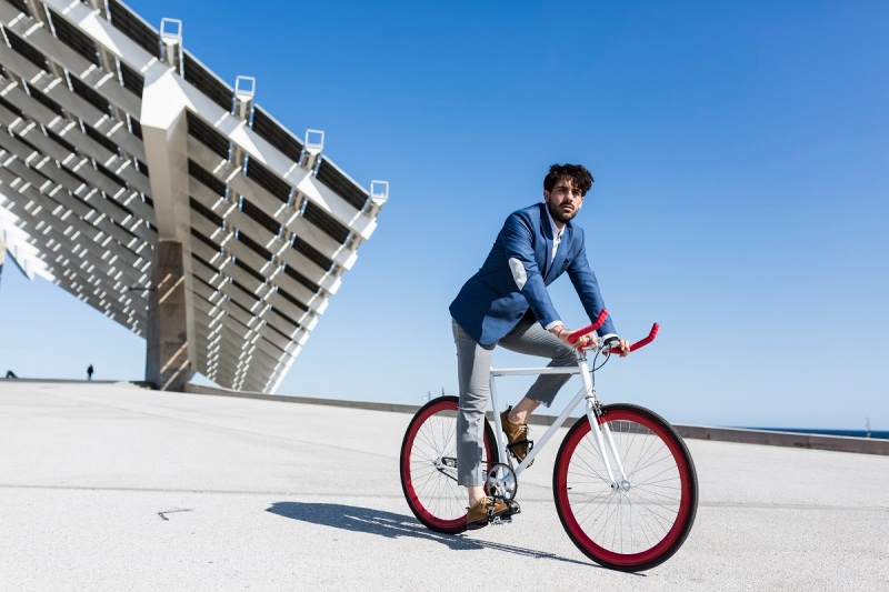 Young businessman on fixie bike outdoors.