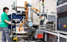 A Universal Robot works in collaboration with workers at MANN+HUMMEL.