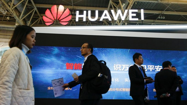 People walk past the stall of the telecommunications equipment maker Huawei Technologies at the Security China 2018 exhibition on public safety and security in Beijing, China October 23, 2018.