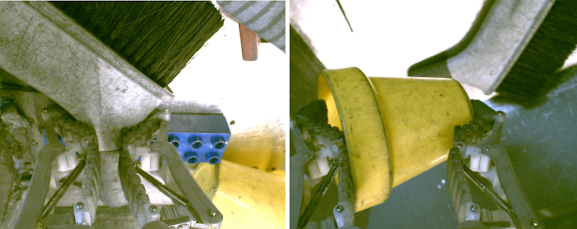 A gripper grasps a brush and yellow cup.