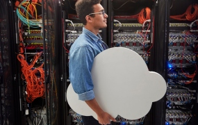 Male IT technician carrying cloud in server room, cloud computing