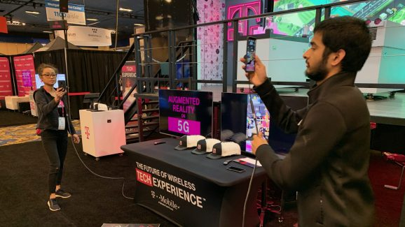 "T-Mobile booth staffers from the University of Washington demonstrate augmented reality over ""5G"" at the 2019 CES in Las Vegas."