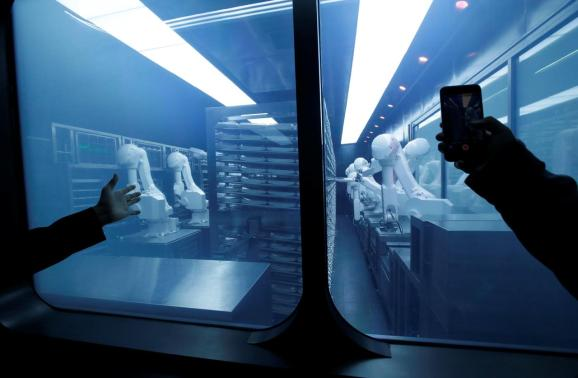 FILE PHOTO: A customer takes a picture as robotic arms collect pre-packaged dishes from a cold storage, done according to the diners' orders, at Haidilao's new artificial intelligence hotpot restaurant in Beijing, China, November 14, 2018.