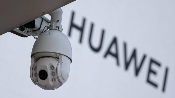 A surveillance camera is seen next to a sign of Huawei outside a shopping mall in Beijing, China January 29, 2019.