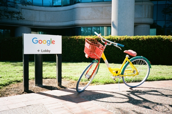 A colorful Google Bike is parked near a sign with logo for Google Inc at the Googleplex, the Silicon Valley headquarters of search engine and technology company Google Inc in Mountain View, California, April 14, 2018. (Photo by Smith Collection/Gado/Getty Images)