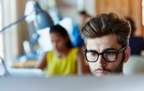 Concentrated young businessman using computer in creative office