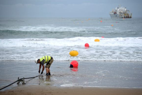 An operator works during the mooring of an undersea fiber optic cable near the Spanish Basque village of Sopelana on June 13, 2017.
