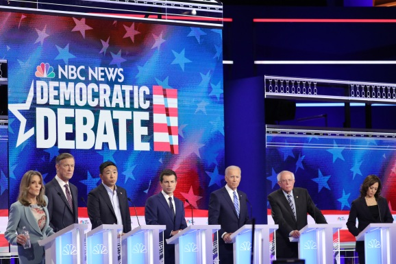 MIAMI, FLORIDA - JUNE 27: Democratic presidential candidates (L-R) Marianne Williamson, former Colorado governor John Hickenlooper, former tech executive Andrew Yang, South Bend, Indiana Mayor Pete Buttigieg, former Vice President Joe Biden, Sen. Bernie Sanders (I-VT), and Sen. Kamala Harris (D-CA) take part in the second night of the first Democratic presidential debate on June 27, 2019 in Miami, Florida.  A field of 20 Democratic presidential candidates was split into two groups of 10 for the first debate of the 2020 election, taking place over two nights at Knight Concert Hall of the Adrienne Arsht Center for the Performing Arts of Miami-Dade County, hosted by NBC News, MSNBC, and Telemundo.