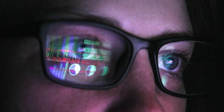 Person wearing glasses with computer screens reflected on the lenses.